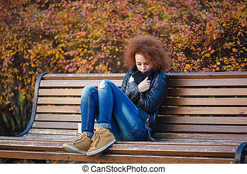 Sad woman sitting on the bench in autumn park