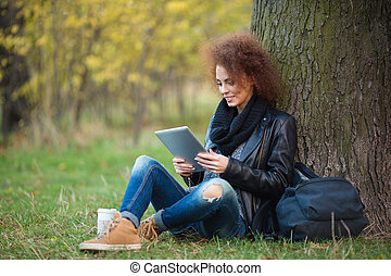 Woman using tablet computer under tree outdoors - Portrait...