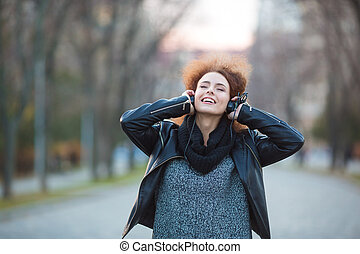 Smiling woman listening music in headphones - Portrait of a...