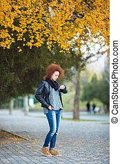 Woman waiting somebody and looking on wrist watch outdoors -...