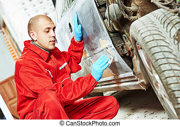 worker applying car body repair putty - auto mechanic worker...