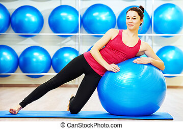 woman doing warm up fitness ball exercise