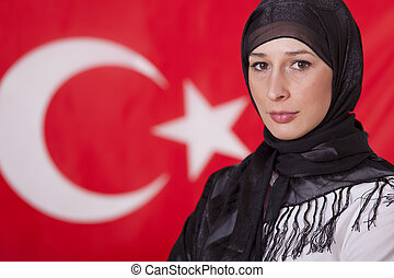 portrait of muslim woman in front of turkish flag