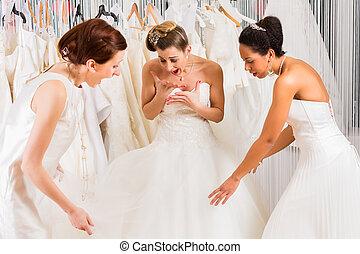 Women having fun during bridal dress fitting in shop - Women...