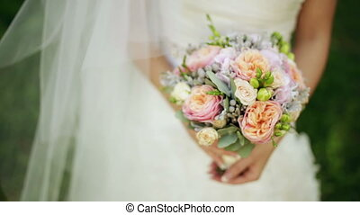 Bride holds a wedding bouquet in her hands Outdoors