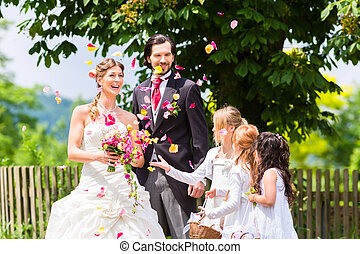 Wedding couple and bridesmaid showering flowers - Wedding...
