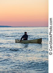 Canoe at sunset - A man canoes at sunset on Georgian Bay,...
