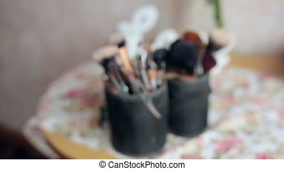 Brush and eye shadow makeup tools on the table