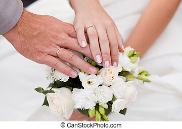 Hands and rings on wedding bouquet - A newly weding couple...