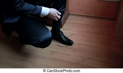 Man tying leather shoes - Man tying patent leather shoes in...