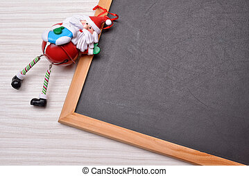 blackboard on wood background with santa claus and copy...