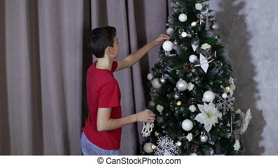 Boy dress up new year xmas tree. He decorate tree with...