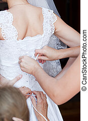 Closeup image of wedding preparations Bridesmaid is helping...