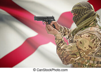Male in muslim keffiyeh with gun in hand and flag on background - Alabama