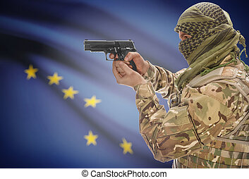 Male in muslim keffiyeh with gun in hand and flag on background - Alaska