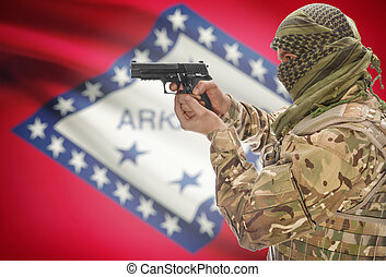 Male in muslim keffiyeh with gun in hand and flag on background - Arkansas