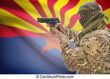 Male in muslim keffiyeh with gun in hand and flag on...