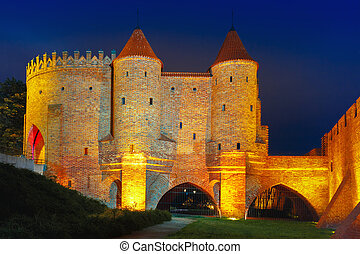 Night Barbican in the Old Town of Warsaw, Poland -...