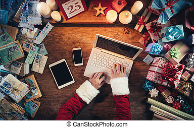 Hi-tech Santa Claus working at his desk and typing on a...