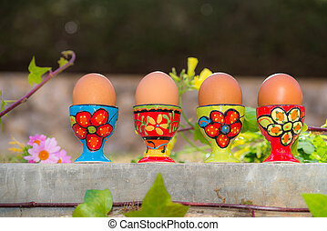 Row of four boiled eggs in colorful egg cups natural...