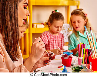 Children with teacher woman painting on paper in  kindergarten .