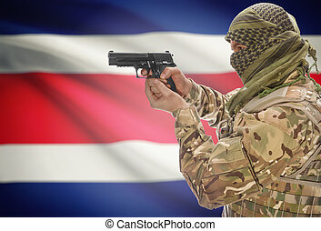 Male in muslim keffiyeh with gun in hand and national flag on background - Costa Rica