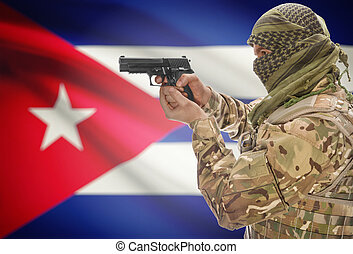 Male in muslim keffiyeh with gun in hand and national flag on background - Cuba
