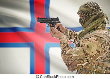 Male in muslim keffiyeh with gun in hand and national flag...