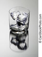 Empty glass tumbler with ice cubes