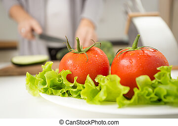 fresh tomatoes lying on lettuce leaves on background of...