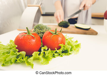 Closeup of fresh tomatoes and lettuce on kitchen table -...