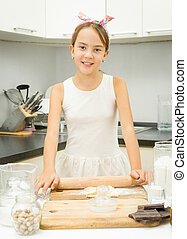 girl rolling dough with wooden pin on kitchen - Cute girl...