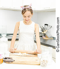 cute girl rolling and kneading dough on wooden board -...