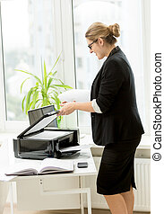 businesswoman in black suit using printer on table -...
