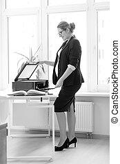 Black and white photo of businesswoman scanning documents -...