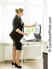 businesswoman in black suit making copies of documents on...