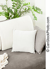 Closeup of white decorative cushion lying on gray sofa at...