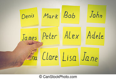 Closeup of woman choosing baby name written on stickers -...