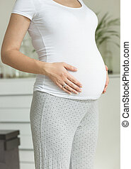 pregnant woman in white t-shirt touching big belly -...