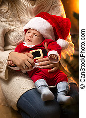Mother holding newborn baby boy in Santa costume at...