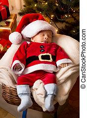 newborn baby boy in Santa Claus costume sleeping in basket -...