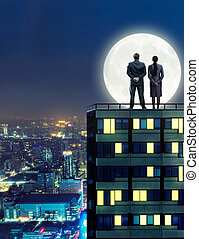 Business peopleon the roof at night - Man and woman look at...