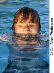 child swims in the outdoor pool - child has fun in the...