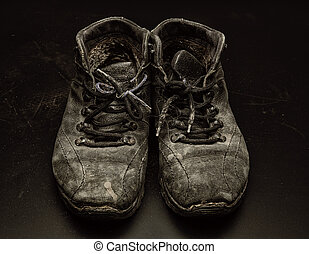 Old worn out shoes on the black floor