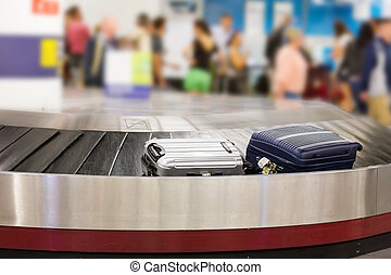 Luggage on the track - Two suitcases on the luggage belt in...