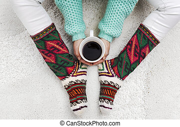 Woman hands holding cup of coffee next to her feet with socks on a white carpet
