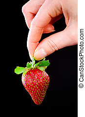 Hand holding a strawberry.