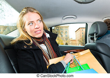 Woman driving in taxi, She was shopping