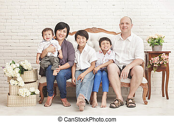 cheerful family at home sitting on sofa