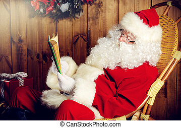 checks the list - Santa Claus sitting in his wooden house in...